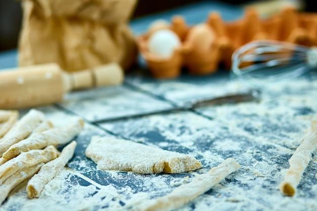 Крупным планом процесс изготовления домашних макаронных изделий. свежее тесто для традиционных итальянских макарон на тонкой ленте. рецепт итальянской кухни. домашняя кухня.