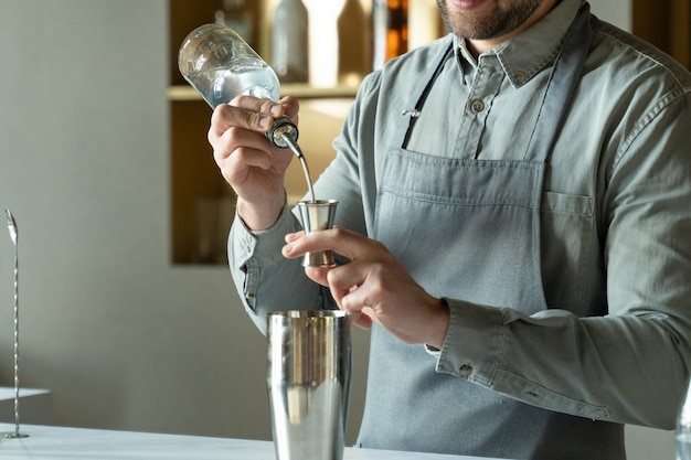 Профессиональный бармен крупным планом наливает ром в шейкер, делая классический коктейль в современном модном баре