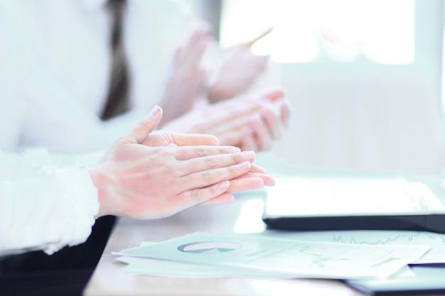 Крупный план. профессиональная бизнес-команда аплодирует спикеру, сидя за своим столом в офисе