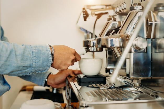 クローズアッププロのコーヒー醸造。レストラン、カフェのバーでコーヒーマシンからセラミックカップに注ぐエスプレッソの側面図。