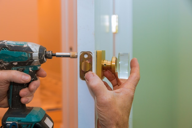 Closeup of a professional locksmith installing or new lock on a house door with screwdriver