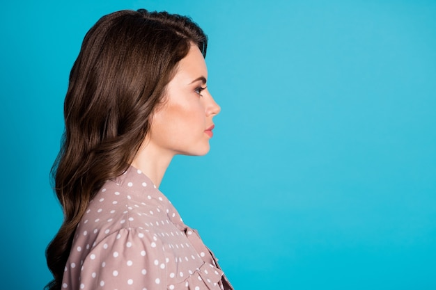 Closeup profile photo of attractive charming chic wavy lady students event party look seriously side empty space wear dotted beige dress isolated pastel blue color background
