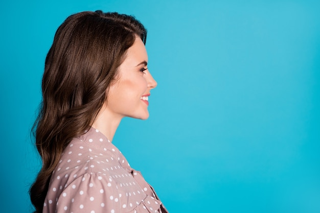 Closeup profile photo of attractive charming chic wavy lady students event party look side empty space beaming smile wear dotted beige dress isolated pastel blue color background