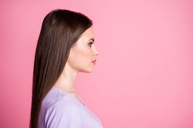 긴 머리를 하고 있는 매력적인 아름다운 여성의 클로즈업 프로필 사진은 치아가 집중되지 않은 채 웃고 있는 빈 공간에 캐주얼 바이올렛 티셔츠를 입고 분리된 분홍색 파스텔 색상 배경입니다.