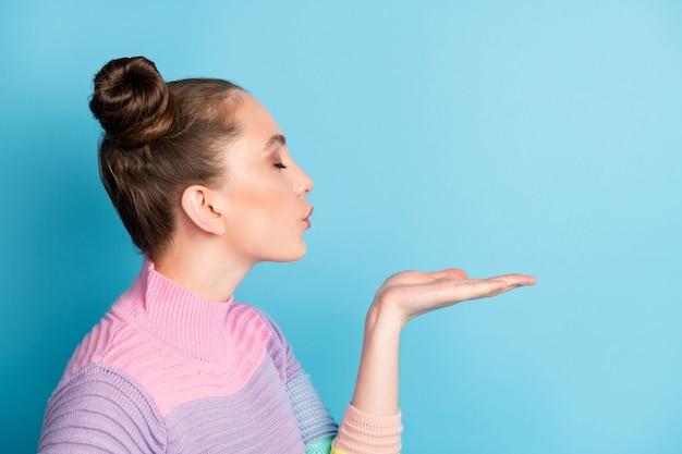 Крупным планом фото профиля привлекательной кокетливой дамы с открытой рукой дует, отправляя воздушные поцелуи, пустое пространство, закрытые глаза, искреннее чувство, носить теплый полосатый свитер, изолированный синий цвет фона
