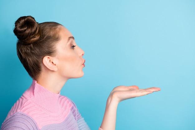 Крупным планом фото профиля привлекательной кокетливой дамы с открытой рукой дует, отправляя воздушные поцелуи стороне пустого пространства, носить повседневный теплый полосатый свитер, изолированный синий цвет фона
