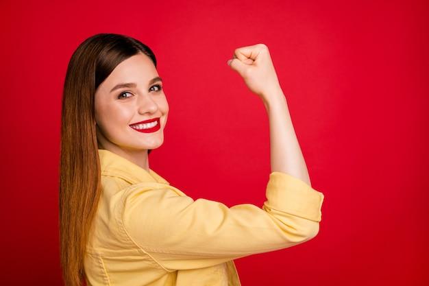 女の子のパワーコンセプトを象徴する完璧な形の強い拳の筋肉を示す魅力的な女性のクローズアッププロフィール写真カジュアルな黄色のデニムブレザージャケット分離された鮮やかな赤い色の背景