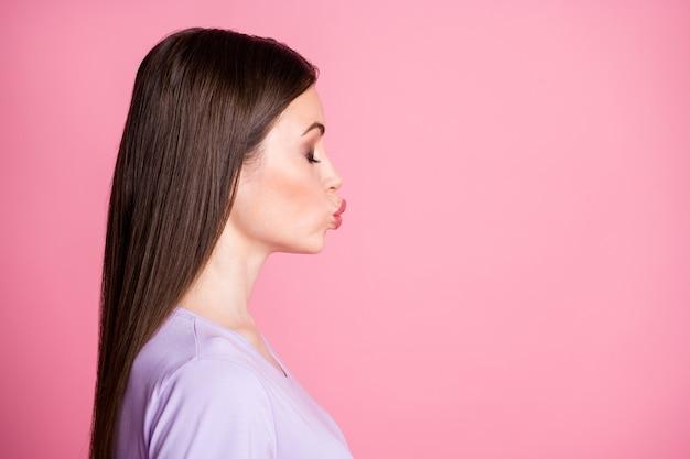 Крупным планом фото профиля привлекательной красивой леди с длинной прической, очаровательной внешностью, посылающей воздушные поцелуи пустое пространство с закрытыми глазами, носить повседневную фиолетовую футболку, изолированную розовым пастельным цветом фона