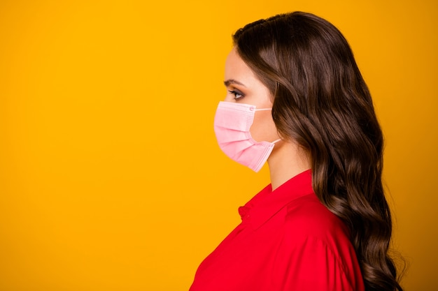 Closeup profile photo of pretty stunning curly business lady bserious bossy person look empty space wear  medical mask office luxury red shirt isolated yellow vivid color background