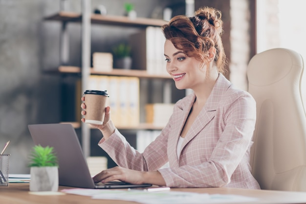 Closeup profile portrait of cheerful smart lady drinking espresso typing article