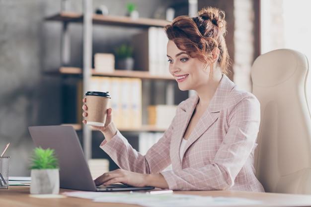 Портрет крупным планом веселой умной леди, пьющей эспрессо, печатающей статью