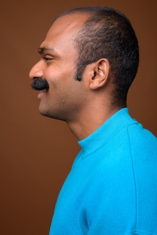 Closeup profile view of happy indian man with mustache wearing blue sweater