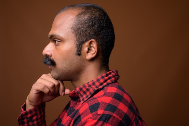 Closeup profile view of indian hipster man with mustache