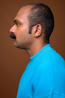 Closeup profile view of indian man with mustache wearing blue sweater