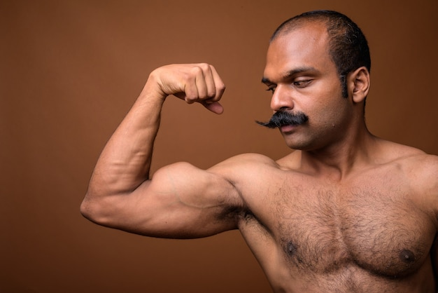 Closeup profile view of muscular indian man with mustache shirtless