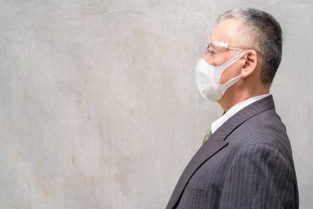マスクと顔のシールドを持つ成熟した日本のビジネスマンの縦断ビューをクローズアップ
