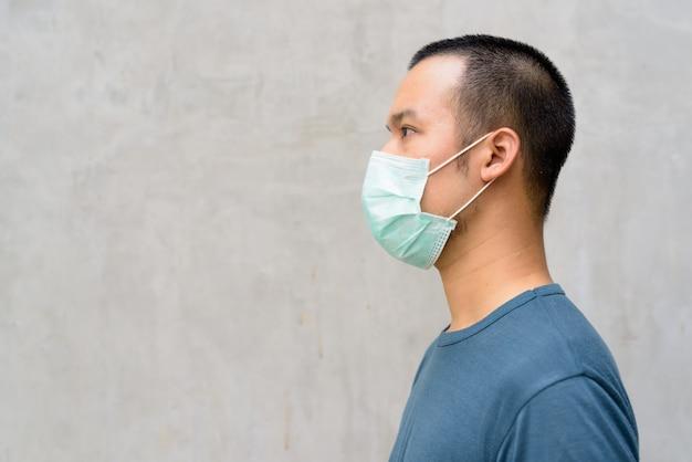 屋外のコロナウイルスの発生からの保護のためのマスクを持つ若いアジア人のクローズアッププロファイルビュー