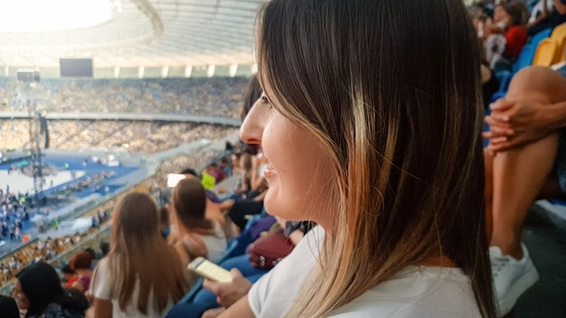 Closeup protrait of beatiful smiling young woman sitting on the stadium and watching music concert on the arena