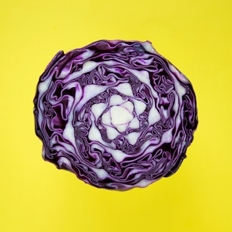 Closeup of purple round cabbage cut in half in a yellow background