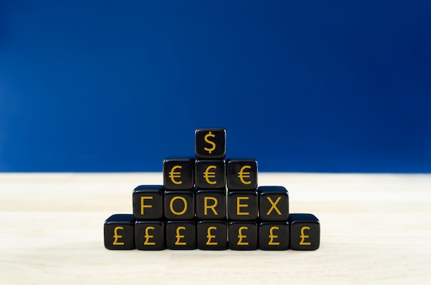 Closeup of a pyramid of black cubes with forex and dollar, euro and pound sterling signs on them. concept of forex currency trading market.
