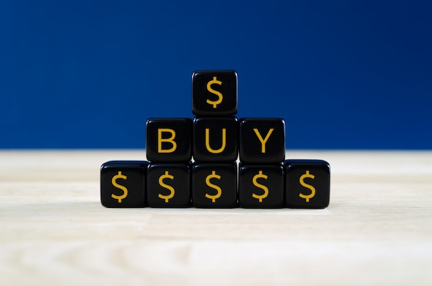 Closeup of a pyramid  of black cubes with gold dollar signs and text buy on them. concept of buy order for financial papers.