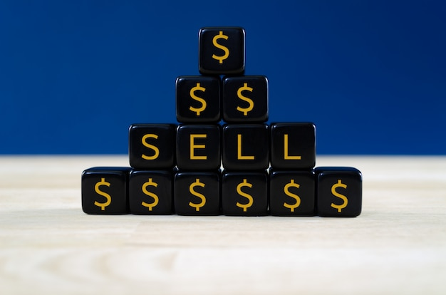 Closeup of a pyramid  of black cubes with gold dollar signs and text sell on them, concept of sell order for financial papers.