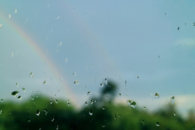 Closeup the rain drops on window's glass with twin rainbows in the backdrop