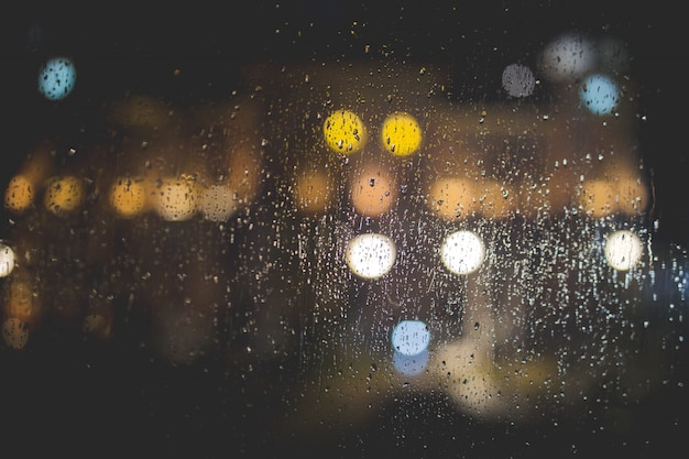Closeup of raindrops on a clear glass window with blurred lights