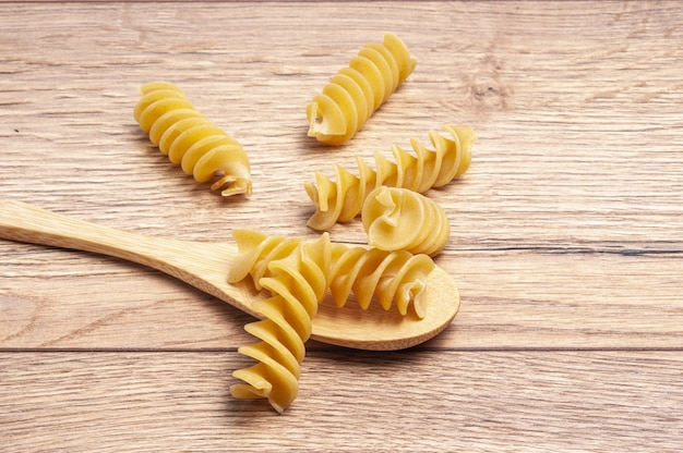 Closeup of raw fusilli with a wooden spoon on the table