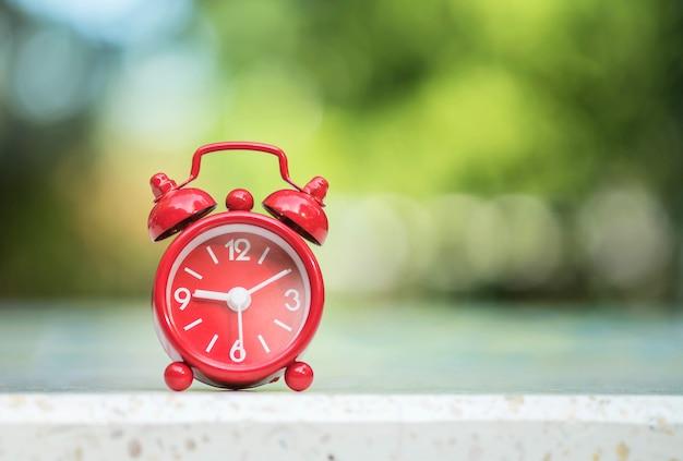 クローズアップの赤い目覚まし時計は、ぼやけた大理石の机と公園の眺めの背景に7時間15分を画面に表示します。