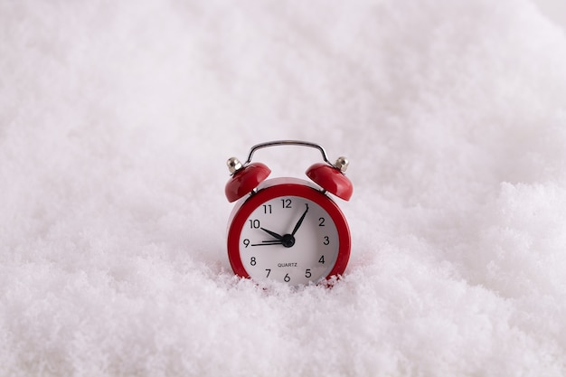 Closeup of a red alarm clock in the snow, a clock counting the time till new year