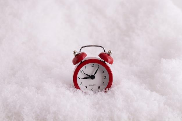 Primo piano di una sveglia rossa nella neve, un orologio che conta il tempo fino al nuovo anno