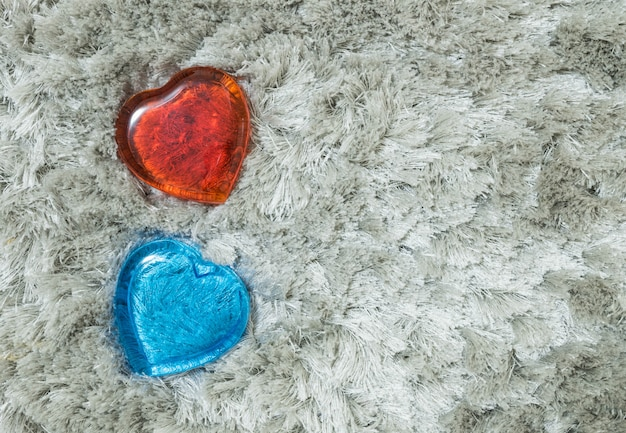 Closeup red and blue glass in heart shape on gray carpet textured background