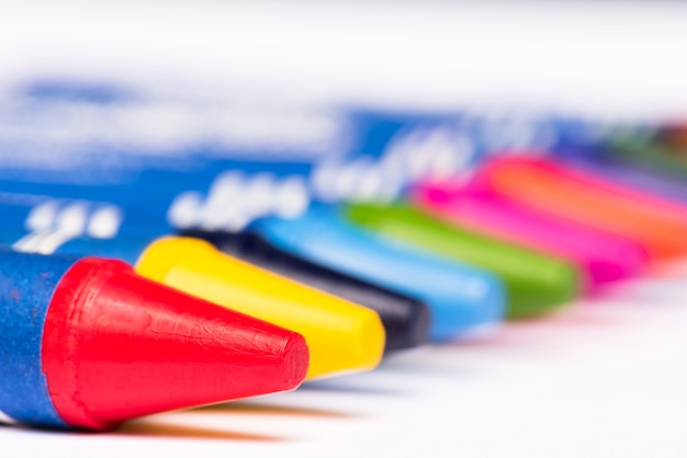 Closeup red crayon witn multicolour crayon in a row