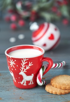 Closeup on red cup of milk with christmas deer design, cookies on dark rustic wooden table with decorations