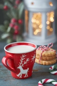 Closeup on red cup of milk with christmas deer design, cookies, xmas lights in lantern and berry