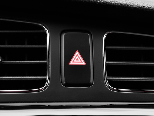 Кнопка выключателя аварийной световой сигнализации крупным планом красная в интерьере современного автомобиля.