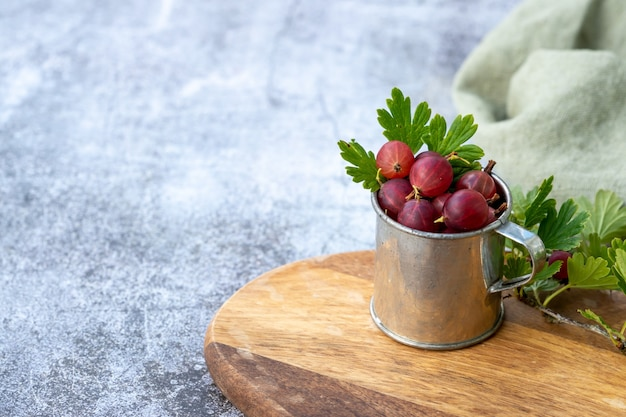 Closeup of red gooseberries in a cup on a wooden board under the lights