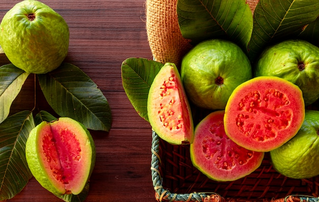 Closeup on red guava sliced with green leaf on rustic wooden table