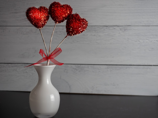 Closeup of a red heart-shaped decorative pop  in a vase against a grey background