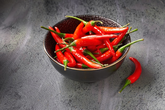 Closeup on red hot chili peppers in ceramic bowl over dark textured table