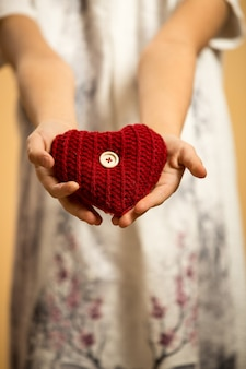 Closeup of red knitted heart lying on girl'ss stretched hands
