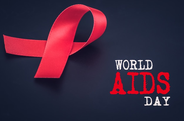 Closeup red ribbon awareness on black background for world aids day campaign