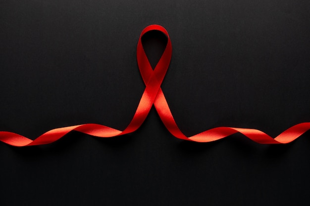 Closeup red ribbon awareness on black paper for world aids day campaign.