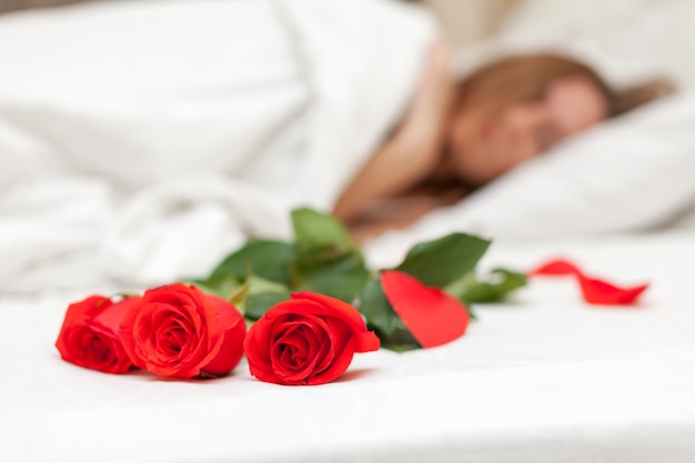 Closeup on red roses near a sleeping woman.