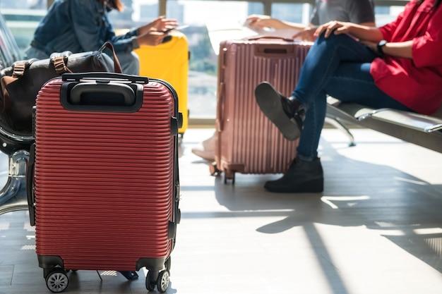 Крупным планом красный чемодан или багаж с размытыми пассажирами сидят на сиденье ожидания, чтобы дождаться вылета в аэропорту. создатель туристического отпуска или отпуск в концепции.