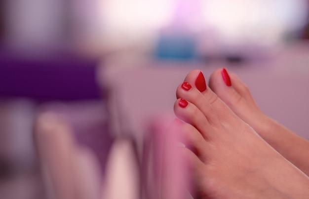 ネイルサロンでの女性の赤い爪をクローズアップ。ネイルとスパサロンで赤いゲル色の足の爪のペディキュア。ネイルサロンでのフットケアと足の爪のトリートメント。フェミニストビジネス。美しさとファッションのコンセプトです。