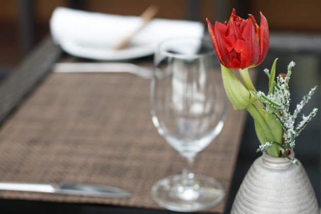 Closeup of a red tulip in a small vase over the table with a wine glass in a cafe or restaurant