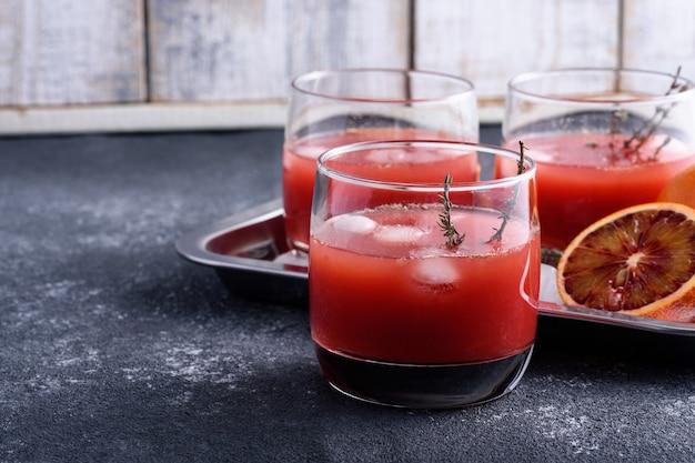灰色の背景、レモネード、ジュースの概念のメガネで赤オレンジのクローズアップさわやかな夏の飲み物