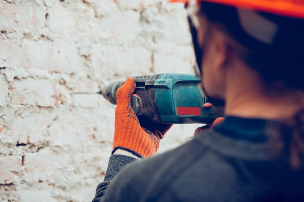 Closeup of repairman in uniform, professional builder working using construction equipment. process of building, apartment renovation, repairing, building. sawing, connecting, cutting, preparing.